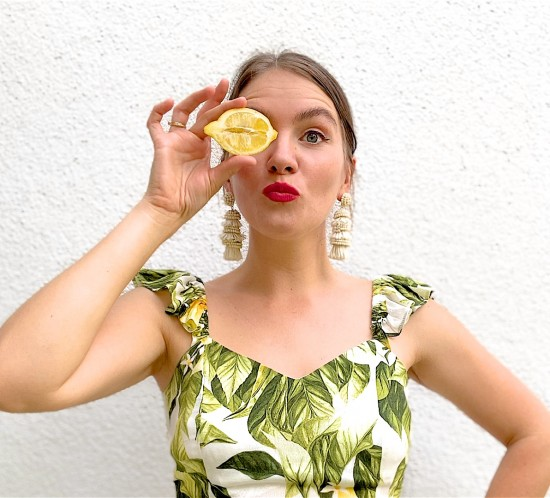 Lemon Print. Fashion Blogger Girl by Style Blog Heartfelt Hunt. Girl with blond, low bun wearing a lemon print top, tassel earrings, straw belt and beige pants.