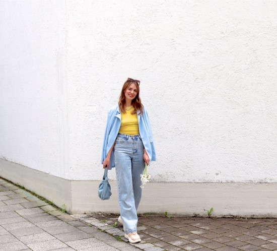 Light Blue Blazer. Fashion Blogger Girl by Style Blog Heartfelt Hunt. Girl with blond hair wearing a light blue blazer, yellow top, wide leg jeans, white bag and chunky sneakers.