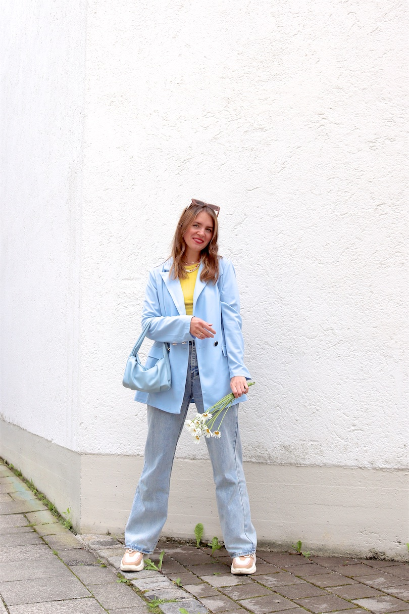 Light Blue Blazer. Fashion and Style Blog Girl from Heartfelt Hunt. Girl with blonde hair wearing a light blue blazer, yellow top, wide leg jeans, white bag and chunky sneakers.