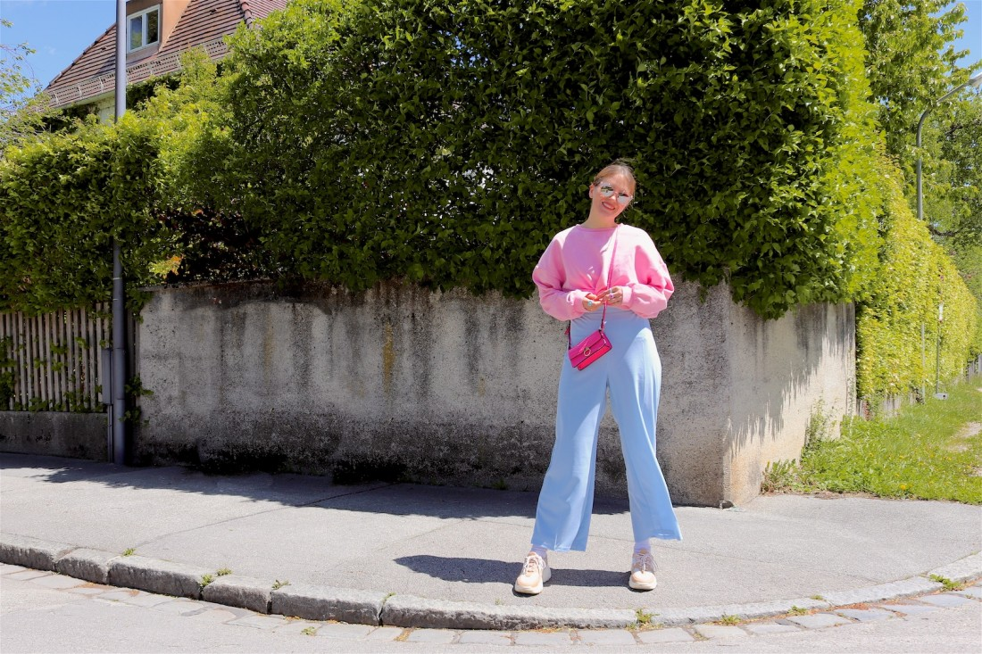 Light Blue Pink. Fashion Blogger Girl by Style Blog Heartfelt Hunt. Girl with blond, low bun wearing light blue pants, pink sweater, pink mini bag, pink sunglasses and chunky sneakers.
