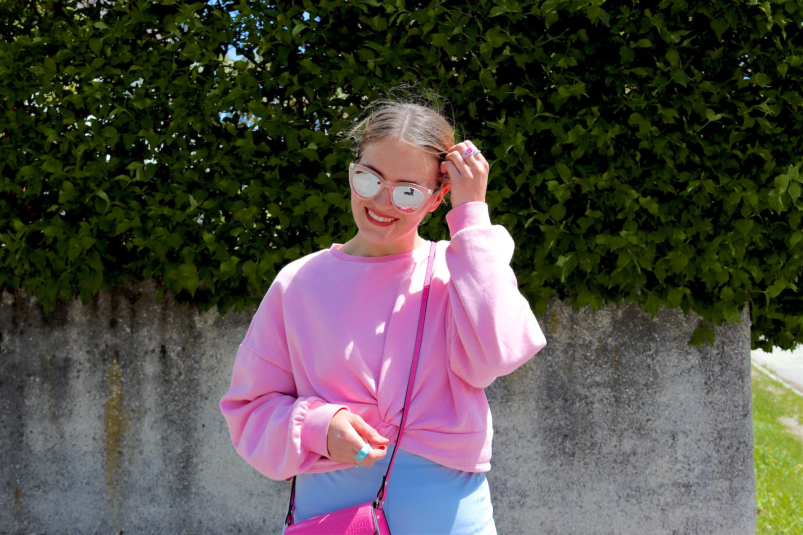 Light Blue Pink. Fashion and Style Blog Girl from Heartfelt Hunt. Girl with blonde, low bun wearing light blue pants, pink sweater, pink mini bag, pink sunglasses and chunky sneakers.