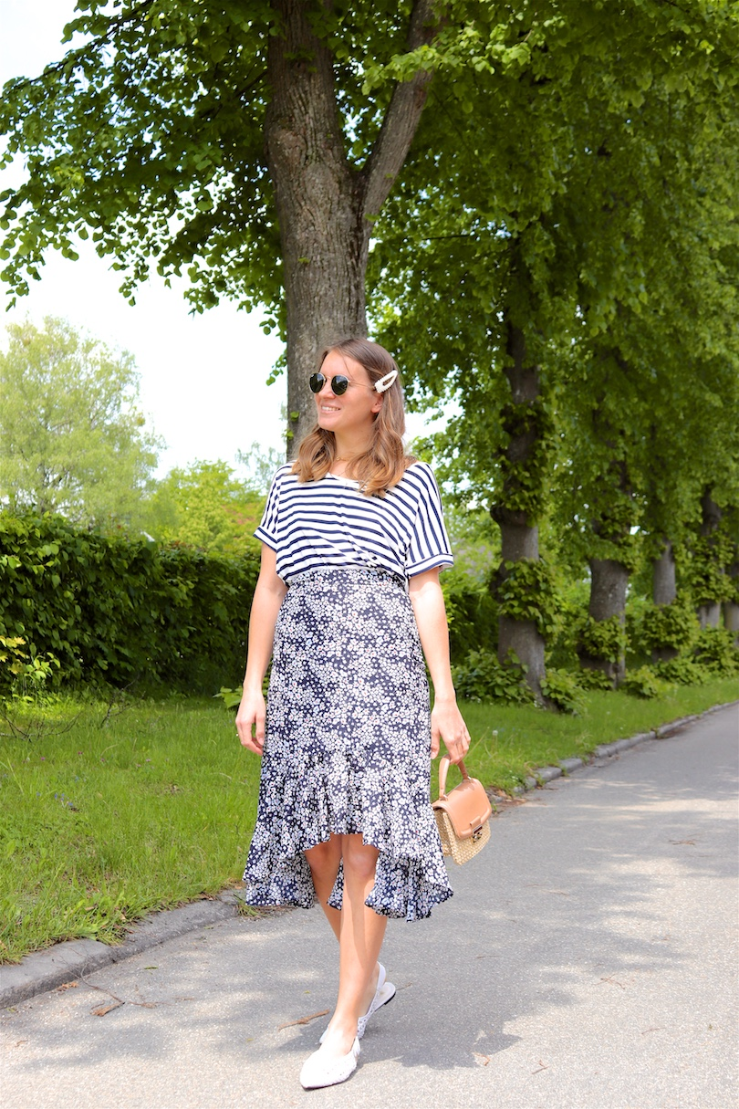Maritime Flowers. Fashion Blogger Girl by Style Blog Heartfelt Hunt. Girl with blond hair and a pearl hair clip wearing a striped top, ruffled skirt with flowers, Ray-Ban sunglasses, straw bag and white flats.