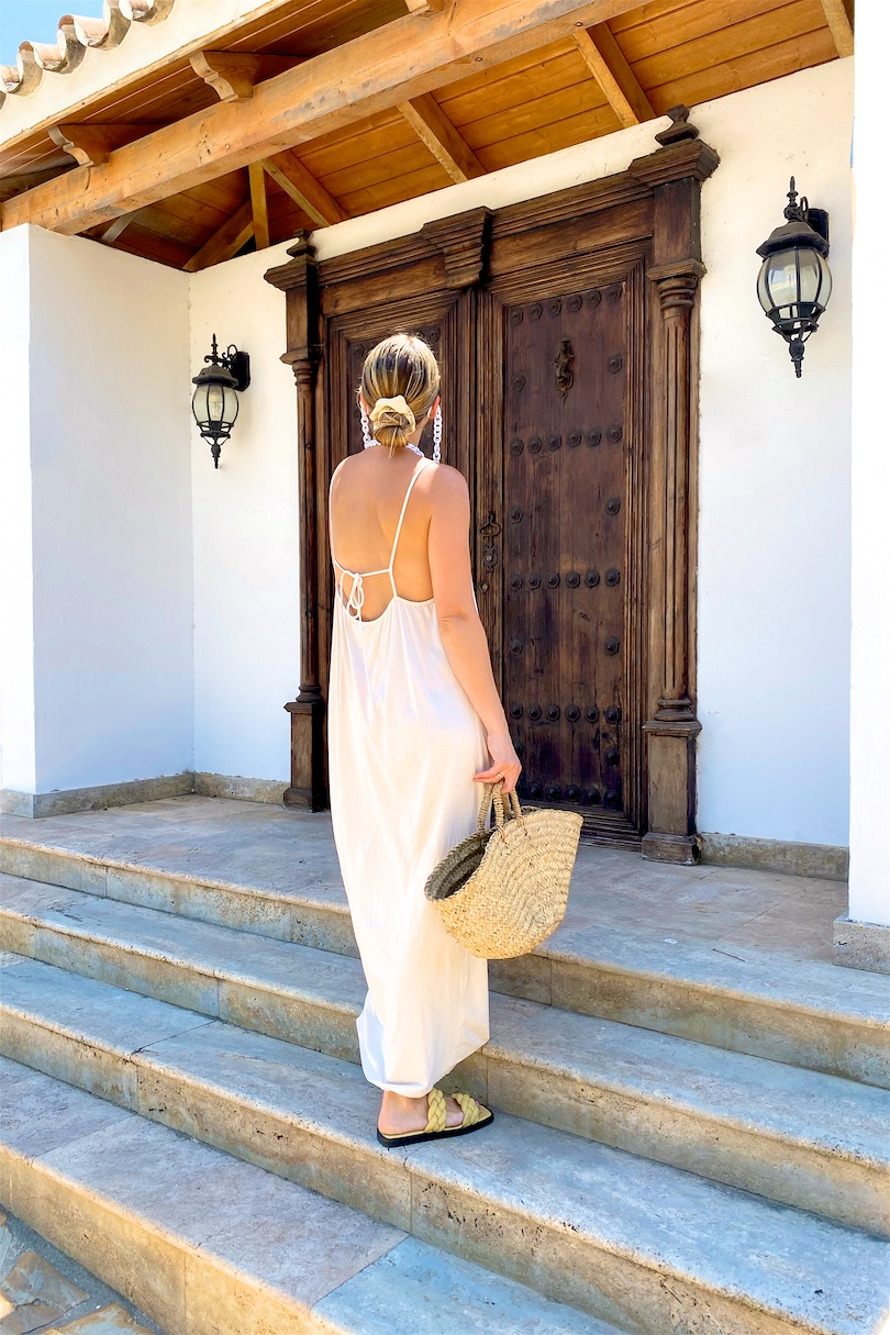 Maxi Summer Dress. Fashion Blogger Girl by Style Blog Heartfelt Hunt. Girl with blond low bun wearing a off-white maxi summer dress, white sunglasses, straw bag and braided sandals.