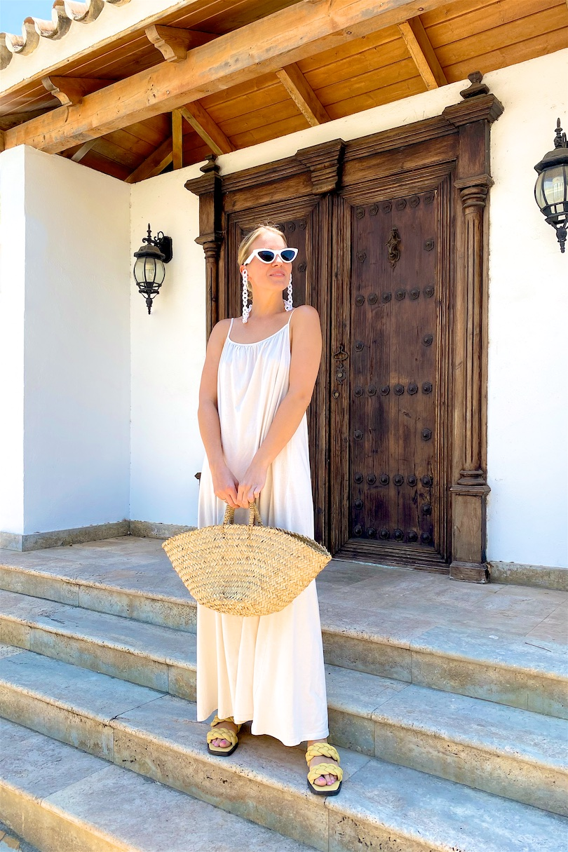 Maxi Summer Dress. Fashion and Style Blog Girl from Heartfelt Hunt. Girl with blonde low bun wearing a off-white maxi summer dress, white sunglasses, straw bag and braided sandals.