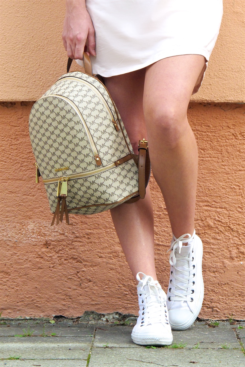 Michael Kors Backpack. Fashion Blogger Girl by Style Blog Heartfelt Hunt. Girl with blond, long hair wearing a Michael Kors backpack, jersey dress, white blouse, cat eye sunglasses and Converse sneakers.