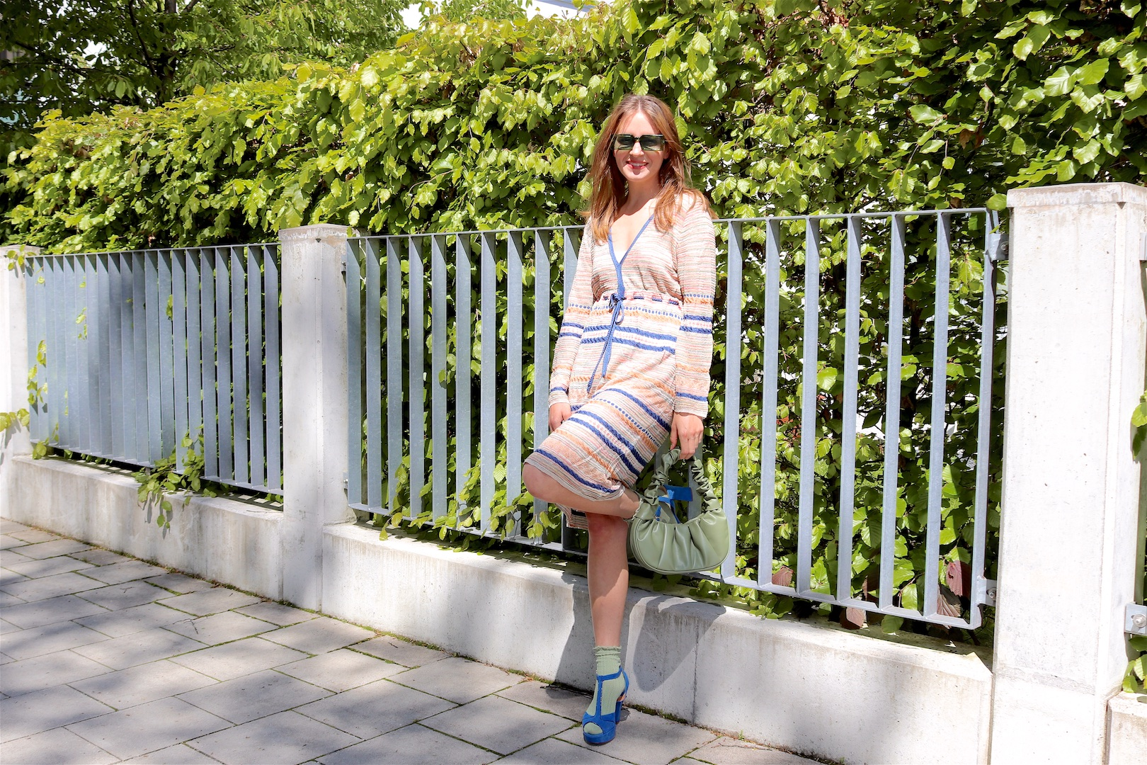 Missoni Dress. Fashion Blogger Girl by Style Blog Heartfelt Hunt. Girl with blond hair wearing a Missoni dress, green sunglasses, green ruched bag, green ruched socks and blue heels.
