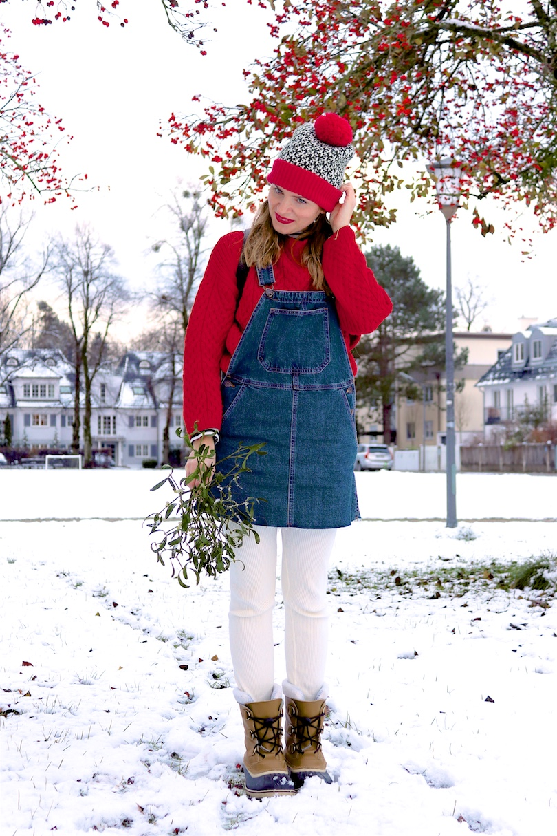 Mistletoe. Fashion and Style Blog Girl from Heartfelt Hunt. Girl with blonde pigtails wearing a red chunky sweater, striped turtleneck top, denim dress, leggings, beanie with pompom, Rebecca Minkoff backpack and Sorel boots.