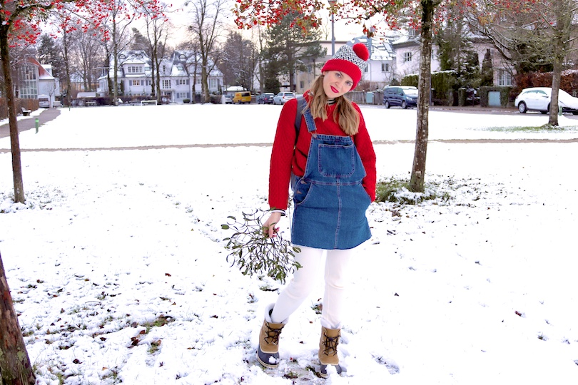 Mistletoe. Fashion Blogger Girl by Style Blog Heartfelt Hunt. Girl with blond pigtails wearing a red chunky sweater, striped turtleneck top, denim dress, leggings, beanie with pompom, Rebecca Minkoff backpack and Sorel boots.
