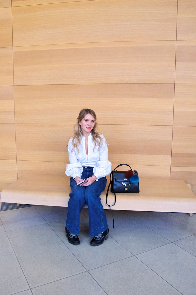 Museum Day. Fashion and Style Blog Girl from Heartfelt Hunt. Girl with blonde, loose curls wearing a white blouse, denim flares, vintage MCM bag with cute fake fur pompons and lace up boots.