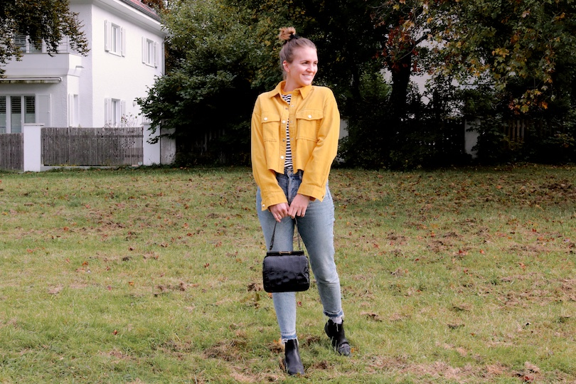 Mustard Corduroy. Fashion Blogger Girl by Style Blog Heartfelt Hunt. Girl with blond, high messy bun and a black velvet scrunchie wearing a mustard corduroy jacket, striped top, mom jeans, black purse and black chelsea boots.