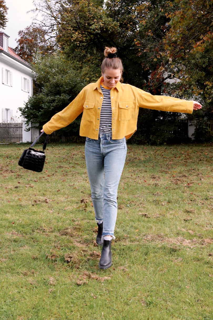 Mustard Corduroy. Fashion and Style Blog Girl from Heartfelt Hunt. Girl with blonde, high messy bun and a black velvet scrunchie wearing a mustard corduroy jacket, striped top, mom jeans, black purse and black chelsea boots.