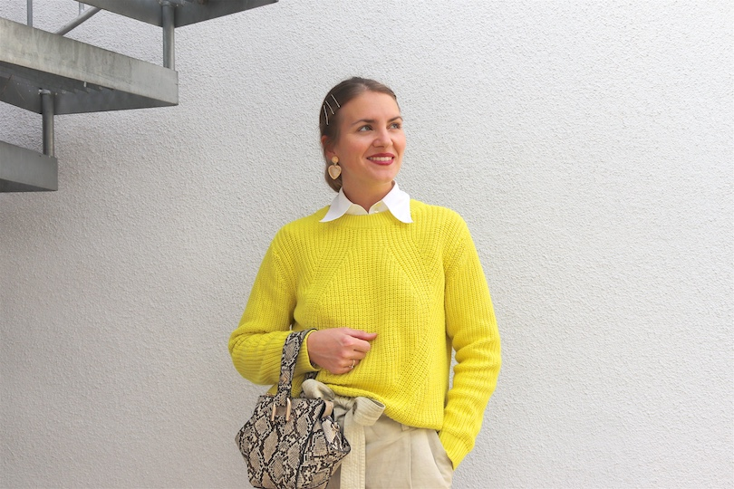 Neon Yellow Sweater. Fashion Blogger Girl by Style Blog Heartfelt Hunt. Girl with blond low bun and bobby pins wearing a neon yellow sweater, white blouse, paperbag pants, golden earrings, snake print bag and white boots.