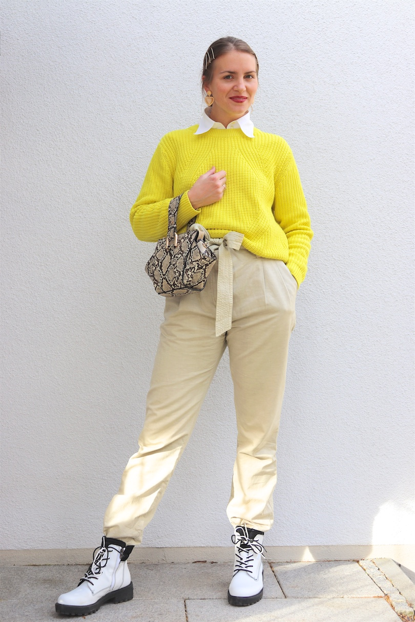 Neon Yellow Sweater. Fashion and Style Blog Girl from Heartfelt Hunt. Girl with blonde low bun and bobby pins wearing a neon yellow sweater, white blouse, paperbag pants, golden earrings, snake print bag and white boots.