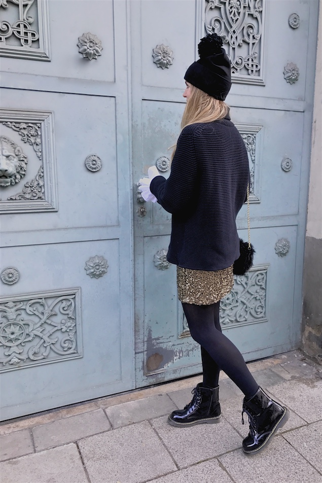 New Year's Eve 2016. Fashion Blogger Girl by Style Blog Heartfelt Hunt. Girl with blond loose curls wearing a heavy knit sweater, blouse with trumpet sleeves, golden sequin dress, pompom beanie, faux fur bag and boots.