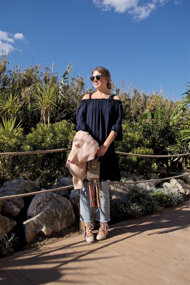 Off Shoulder Dress. Fashion and Style Blog Girl from Heartfelt Hunt. Girl with blonde low bun wearing a off shoulder dress, cropped flare jeans, lace up shoes, Ray-Ban sunglasses and Chloé fringe bag.