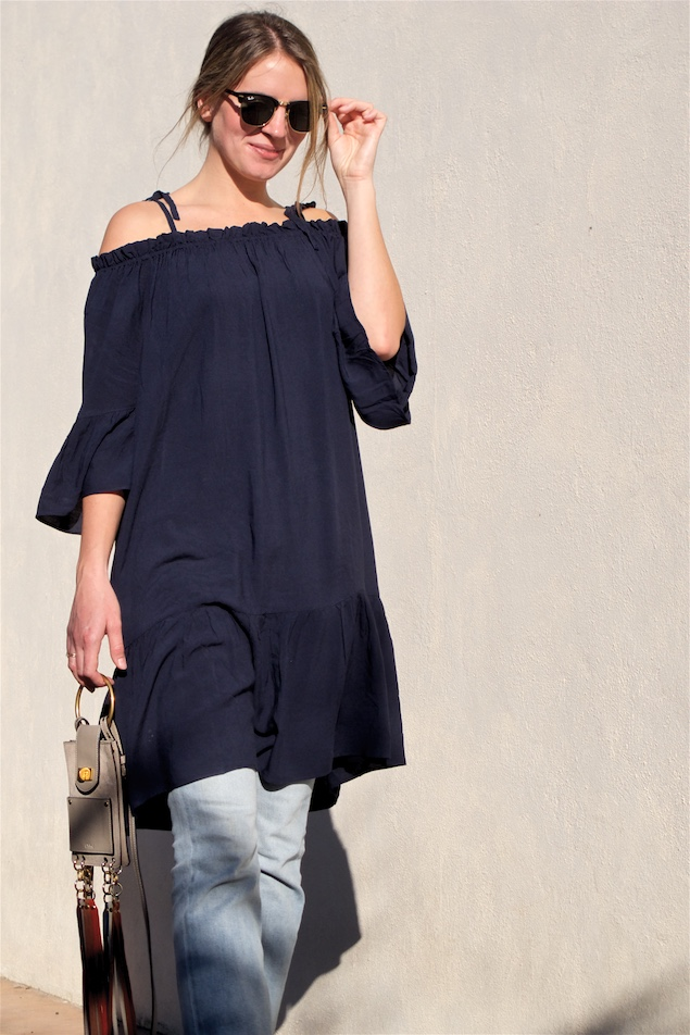 Off Shoulder Dress. Fashion Blogger Girl by Style Blog Heartfelt Hunt. Girl with blond low bun wearing a off shoulder dress, cropped flare jeans, lace up shoes, Ray-Ban sunglasses and Chloé fringe bag.