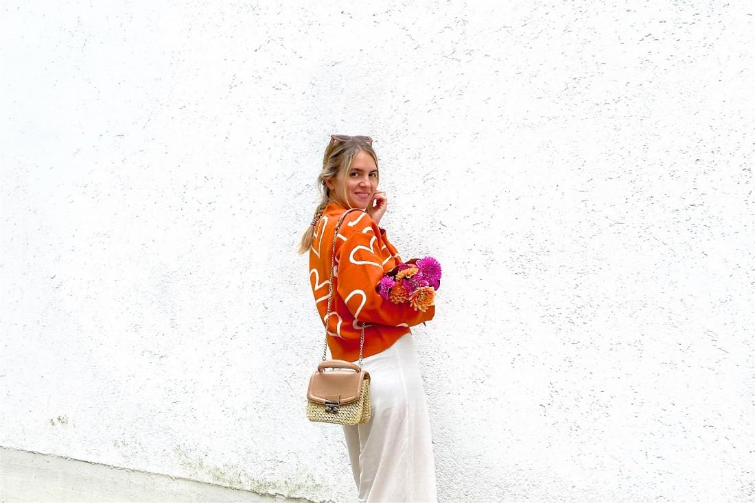 Orange Cardigan. Fashion Blogger Girl by Style Blog Heartfelt Hunt. Girl with blond dutch braid wearing an orange cardigan, wide leg pants, slim sunglasses, straw bag, orange socks and chunky sneakers.