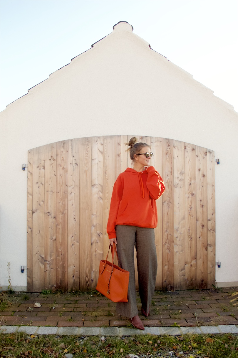Orange Hoodie. Fashion and Style Blog Girl from Heartfelt Hunt. Girl with blonde high, messy bun wearing an orange hoodie, flared pants, Ray-Ban sunglasses, orange Michael Kors bag and heeled boots.