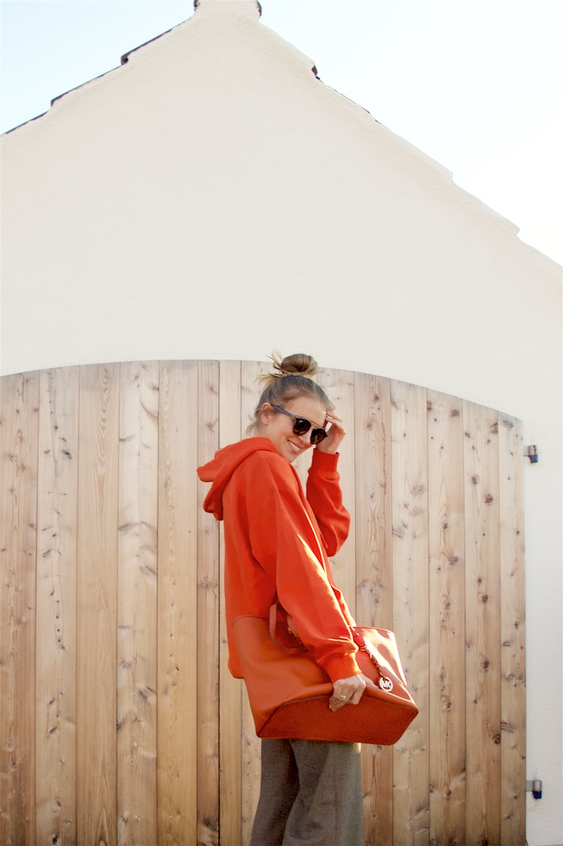 Orange Hoodie. Fashion Blogger Girl by Style Blog Heartfelt Hunt. Girl with blond high, messy bun wearing an orange hoodie, flared pants, Ray-Ban sunglasses, orange Michael Kors bag and heeled boots.