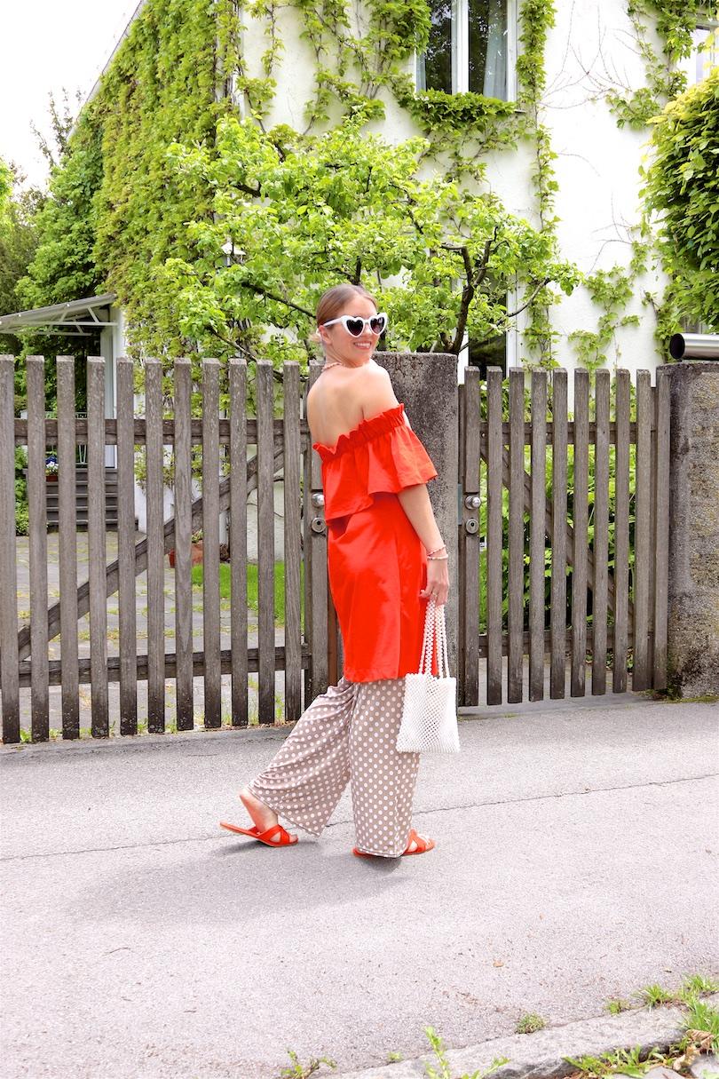 Orange & Polka Dots. Fashion Blogger Girl by Style Blog Heartfelt Hunt. Girl with blond, low bun wearing an orange off-shoulder dress, polka dot pants, white heart shaped sunglasses, pearl bag and orange sandals.