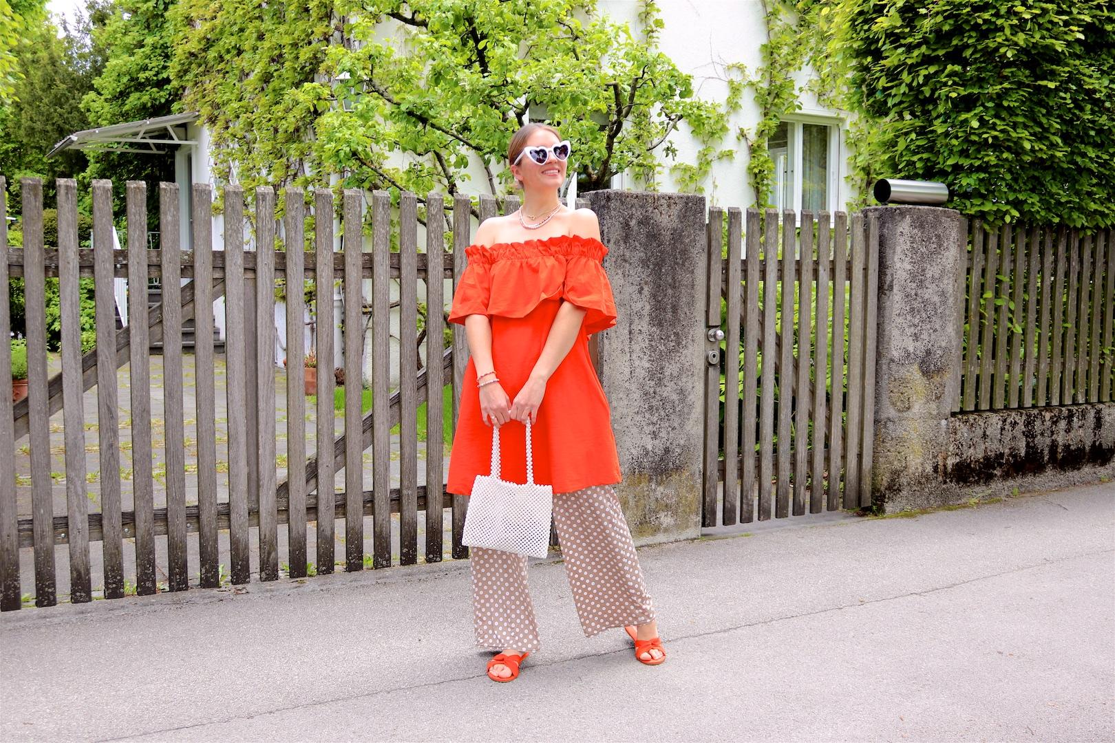 Orange & Polka Dots. Fashion and Style Blog Girl from Heartfelt Hunt. Girl with blonde, low bun wearing an orange off-shoulder dress, polka dot pants, white heart shaped sunglasses, pearl bag and orange sandals.