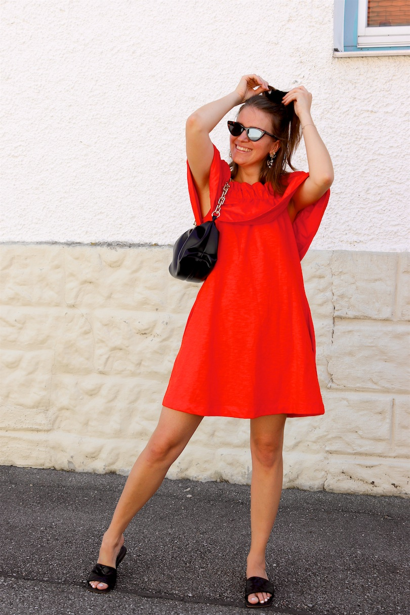 Orange Summer Dress. Fashion Blogger Girl by Style Blog Heartfelt Hunt. Girl with blond half-up half-down hairstyle bun wearing an orange summer dress, slim cat-eye sunglasses, pouch bag and sandals.