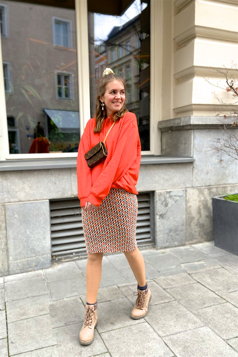 Orange Vibes. Fashion and Style Blog Girl from Heartfelt Hunt. Girl with blonde half-up half-down messy bun and scrunchie wearing an orange hoodie, patterned skirt, earrings, Louis Vuitton belt bag, boots.