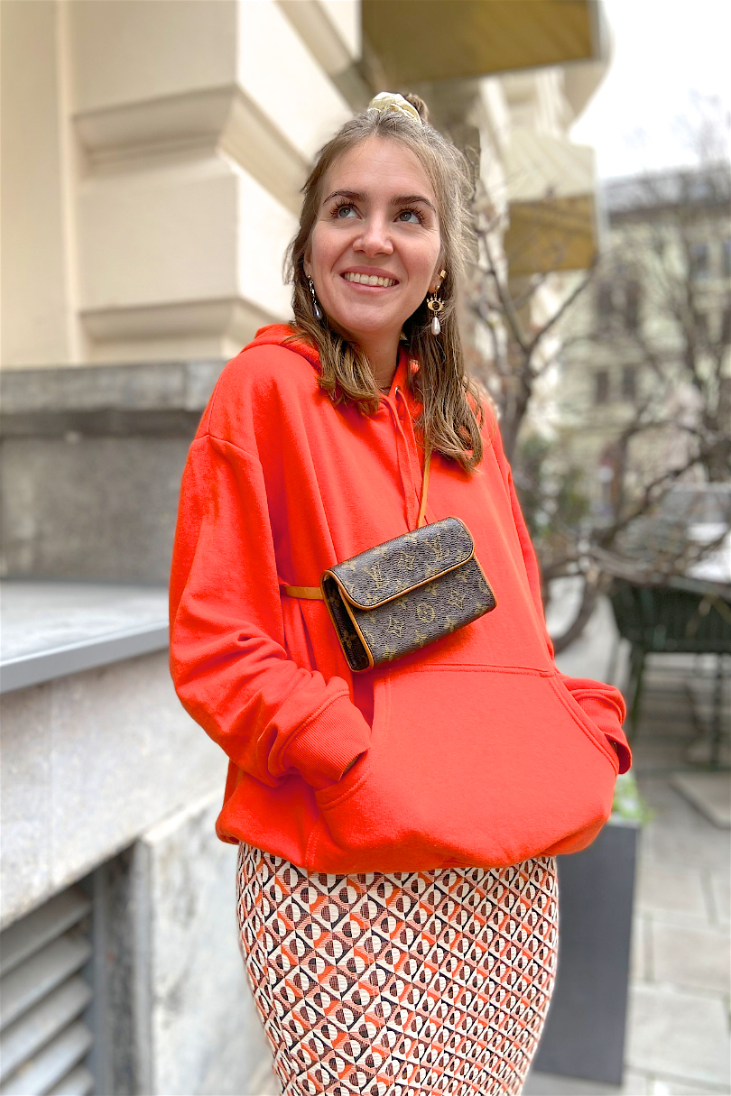 Orange Vibes. Fashion Blogger Girl by Style Blog Heartfelt Hunt. Girl with blond half-up half-down messy bun and scrunchie wearing an orange hoodie, patterned skirt, earrings, Louis Vuitton belt bag, boots.