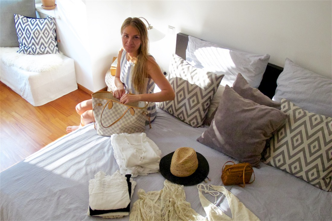 Packing Day. Fashion Blogger Girl by Style Blog Heartfelt Hunt. Girl with blond hair wearing a striped linen dress, showing a white lace-up dress, white swimsuit, crochet cardigan, straw hat, straw bag, marbled sunglasses and Ray-Ban sunglasses.