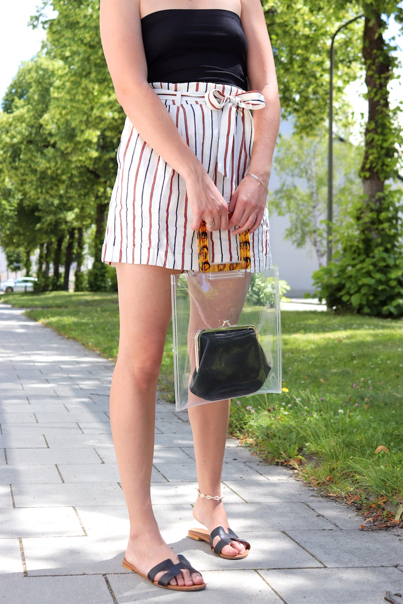Paperbag Shorts. Fashion and Style Blog Girl from Heartfelt Hunt. Girl with blonde hair wearing paperbag shorts, black top, Ray-Ban sunglasses, pearl earrings, transparent bag and black sandals.