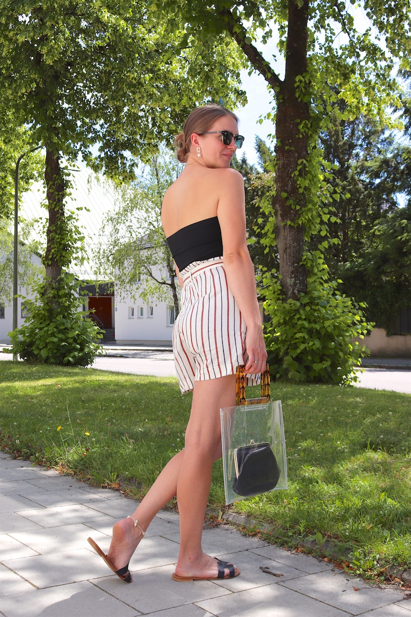 Paperbag Shorts. Fashion Blogger Girl by Style Blog Heartfelt Hunt. Girl with blond hair wearing paperbag shorts, black top, Ray-Ban sunglasses, pearl earrings, transparent bag and black sandals.