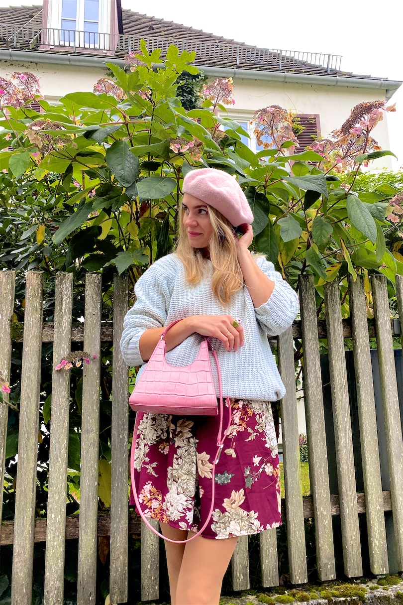 Pastel For Fall. Fashion and Style Blog Girl from Heartfelt Hunt. Girl with blonde hair wearing a mint pastel sweater, pastel pink beret, floral dress, pink Staud bag and off-white loafers.
