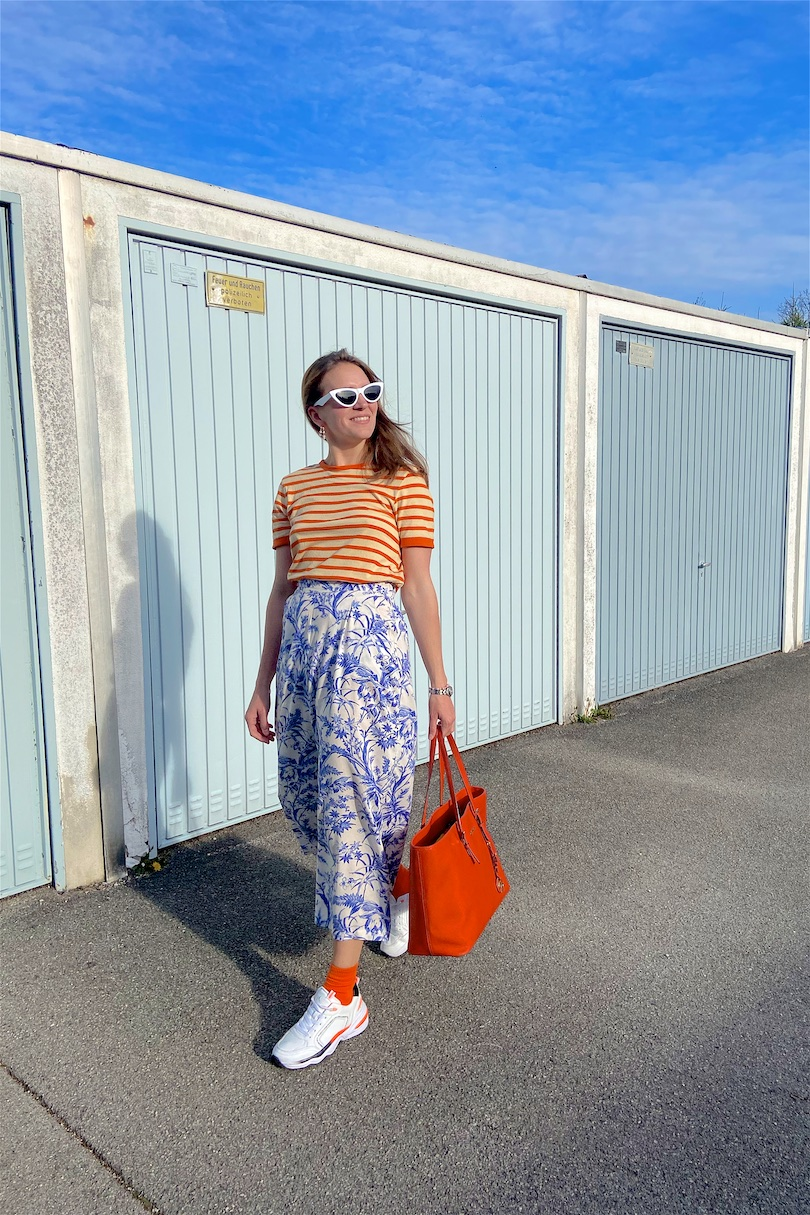 Pattern Mix. Fashion Blogger Girl by Style Blog Heartfelt Hunt. Girl with blond hair wearing a striped T-shirt, floral pants, white slim sunglasses, orange Michael Kors bag, colorful socks and chunky sneakers.