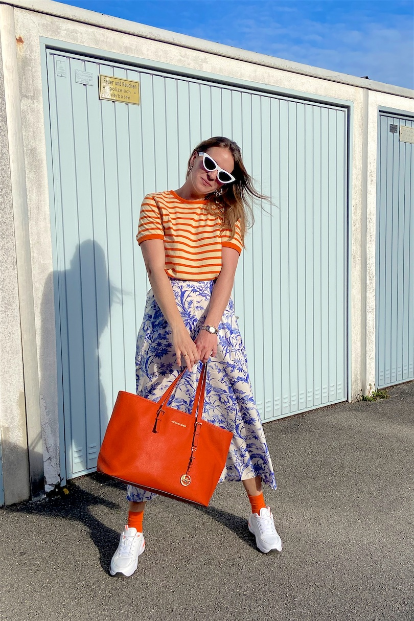 Pattern Mix. Fashion and Style Blog Girl from Heartfelt Hunt. Girl with blonde hair wearing a striped T-shirt, floral pants, white slim sunglasses, orange Michael Kors bag, colorful socks and chunky sneakers.