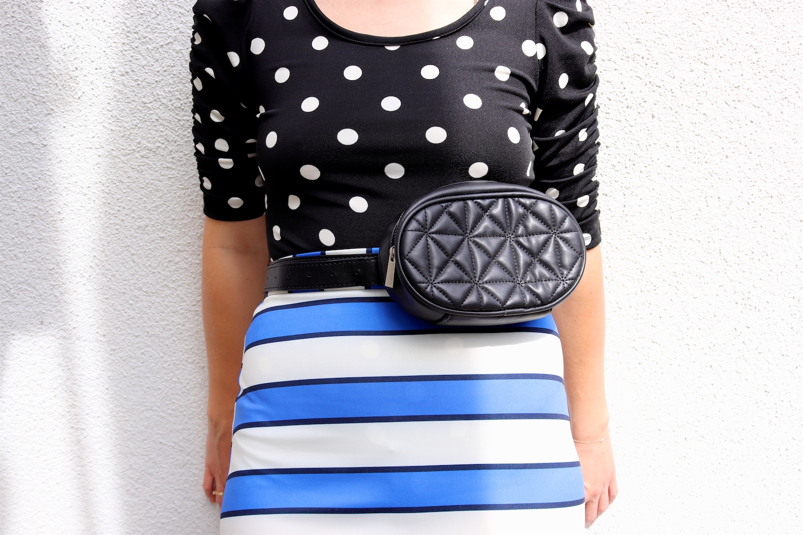 Pattern Mix. Fashion Blogger Girl by Style Blog Heartfelt Hunt. Girl with blond, long bob wearing a polka dot top, striped skirt, rhinestone earrings, belt bag and studded mules.