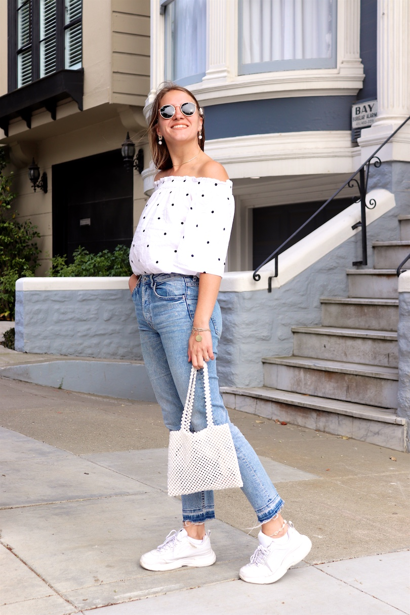 Pearl Bag. Fashion and Style Blog Girl from Heartfelt Hunt. Girl with blonde hair and pearl hair clip wearing a pearl bag, polka dot top, mom jeans, pearl earrings, Ray-Ban sunglasses and chunky sneakers.
