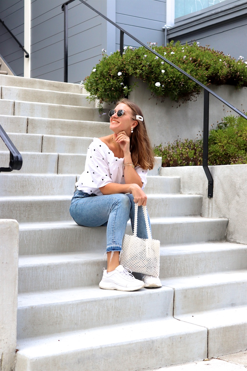Pearl Bag. Fashion Blogger Girl by Style Blog Heartfelt Hunt. Girl with blond hair and pearl hair clip wearing a pearl bag, polka dot top, mom jeans, pearl earrings, Ray-Ban sunglasses and chunky sneakers.