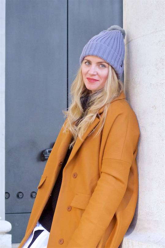 Perfect Winter Coat. Fashion Blogger Girl by Style Blog Heartfelt Hunt. Girl with blond, loose curls wearing her perfect winter coat, oversized sweater, long blouse, lace skirt, pompon beanie and shiny boots.