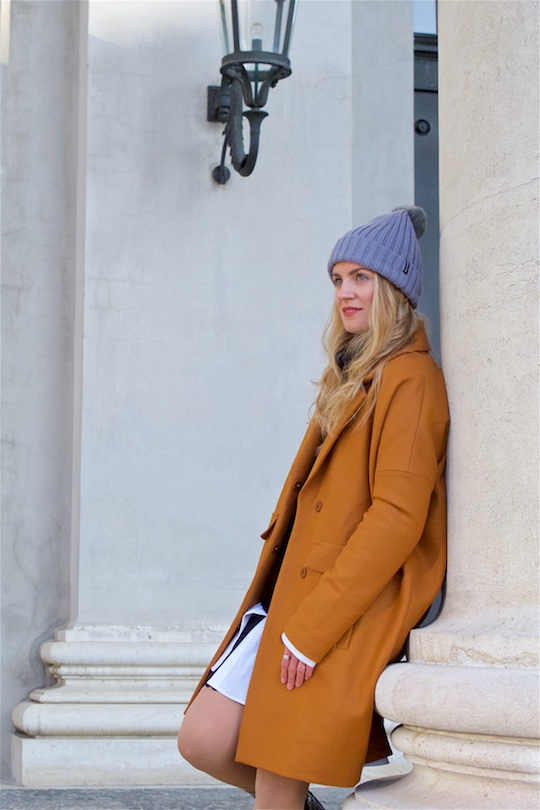 Perfect Winter Coat. Fashion and Style Blog Girl from Heartfelt Hunt. Girl with blonde, loose curls wearing her perfect winter coat, oversized sweater, long blouse, lace skirt, pompon beanie and shiny boots.