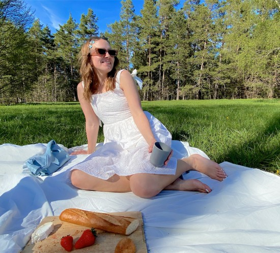 Picnic Day. Fashion Blogger Girl by Style Blog Heartfelt Hunt. Girl with blond, loose curls wearing a white lace dress, slim sunglasses and light blue bag.