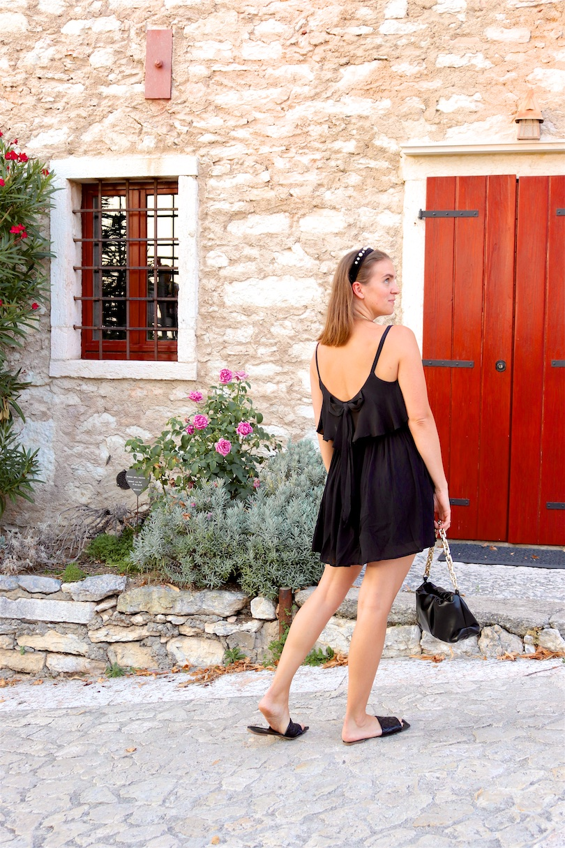 Pieve Di San Giorgio Di Valpolicella. Fashion Blogger Girl by Style Blog Heartfelt Hunt. Girl with blond hair and pearl headband wearing a little black dress, pouch bag and sandals.