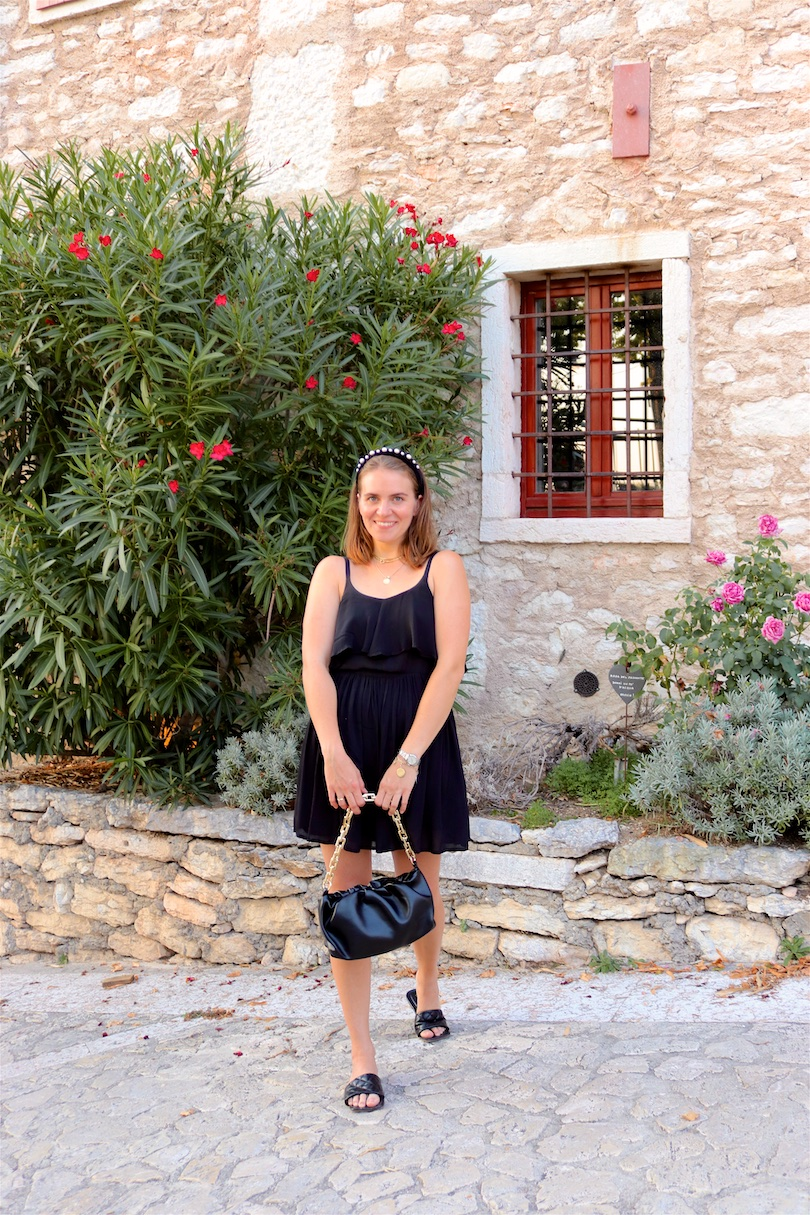 Pieve Di San Giorgio Di Valpolicella. Fashion and Style Blog Girl from Heartfelt Hunt. Girl with blonde hair and pearl headband wearing a little black dress, pouch bag and sandals.