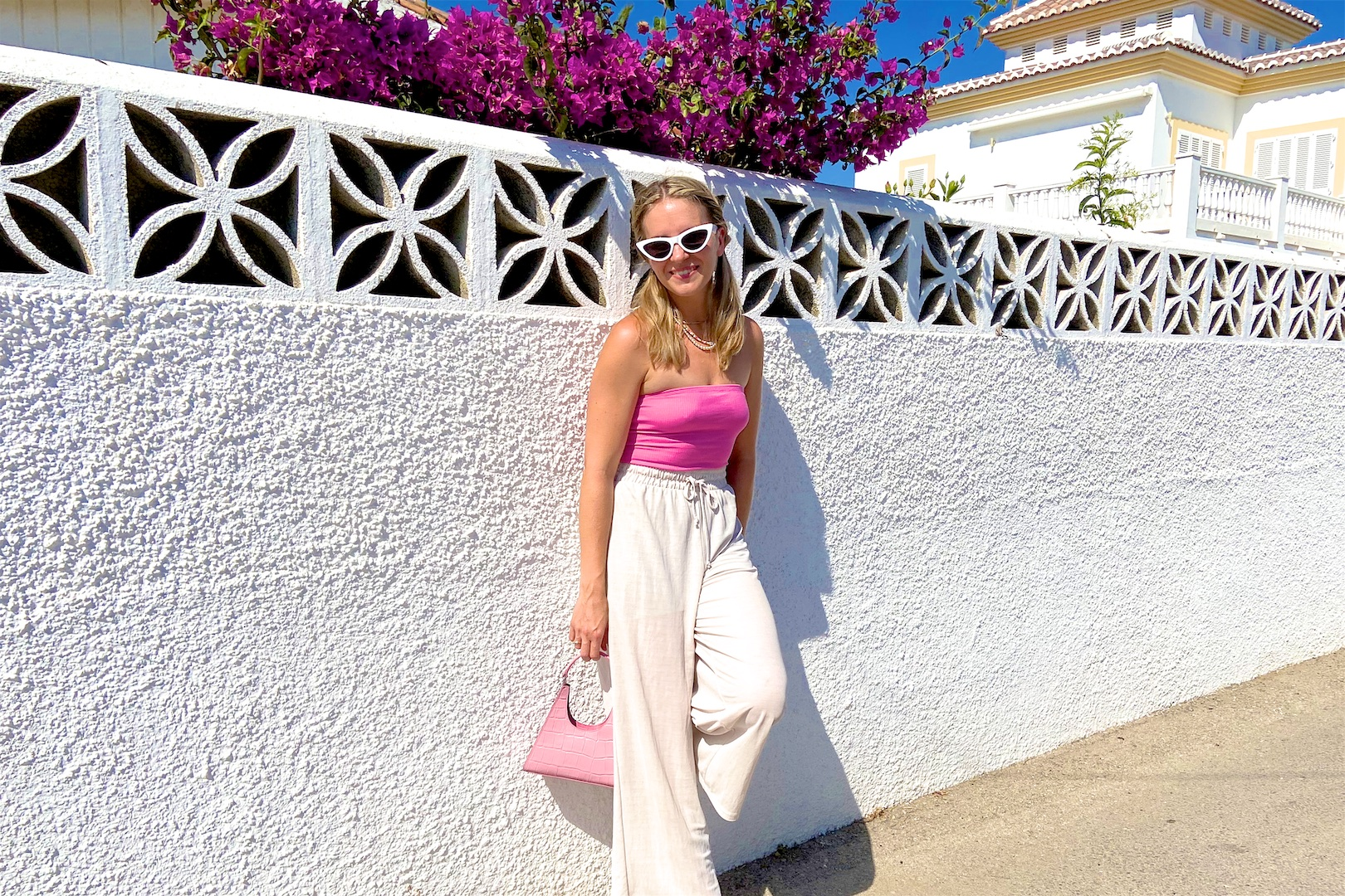 Pink Bag. Fashion Blogger Girl by Style Blog Heartfelt Hunt. Girl with blond braids wearing a pink bag, pink top, white sunglasses, wide leg pants and pink sandals.