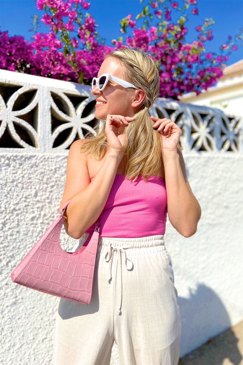 Pink Bag. Fashion and Style Blog Girl from Heartfelt Hunt. Girl with blonde braids wearing a pink bag, pink top, white sunglasses, wide leg pants and pink sandals.