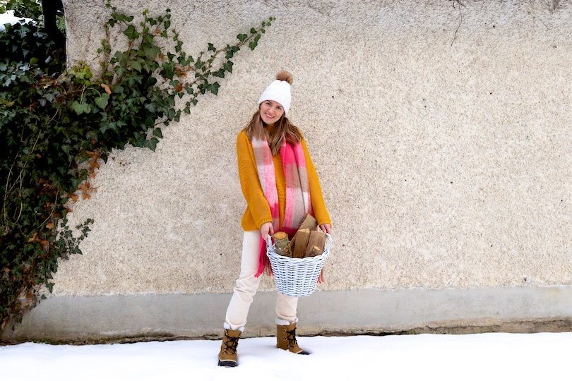 Pink Checked Scarf. Fashion Blogger Girl by Style Blog Heartfelt Hunt. Girl with blond hair wearing a pink checked scarf, yellow sweater, off-white corduroy pants, beanie with faux fur pompom and Sorel boots.