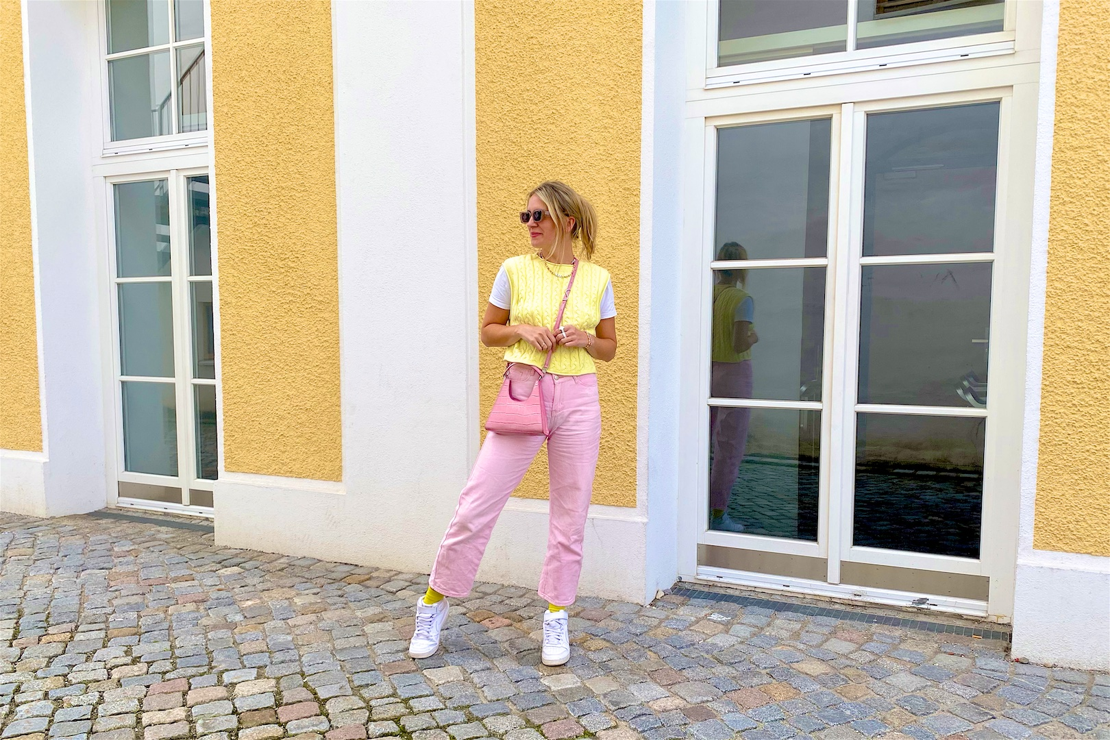 Pink Denim. Fashion Blogger Girl by Style Blog Heartfelt Hunt. Girl with blond hair and pink hair claw clip wearing pink denim, knitted vest, pink Staud bag, yellow socks and Nike sneakers.
