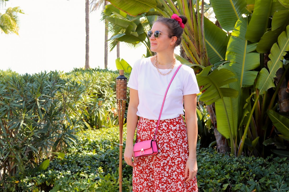 Pink Floral. Fashion Blogger Girl by Style Blog Heartfelt Hunt. Girl with blond, high, messy bun and pink scrunchie wearing a pink bag, Ray-Ban sunglasses, floral skirt, statement necklace, white tee and chunky sneakers.