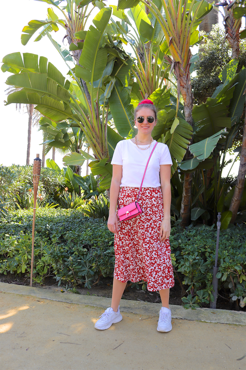 Pink Floral. Fashion and Style Blog Girl from Heartfelt Hunt. Girl with blonde, high, messy bun and pink scrunchie wearing a pink bag, Ray-Ban sunglasses, floral skirt, statement necklace, white tee and chunky sneakers.