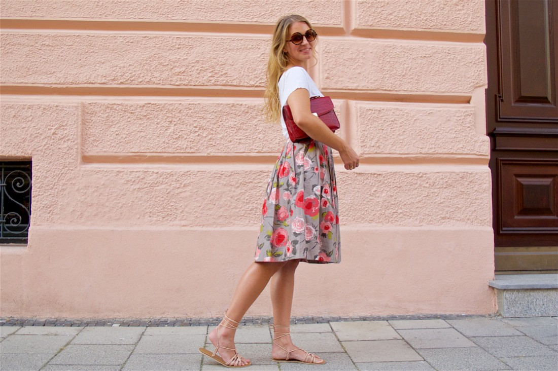 Pink Flowers. Fashion Blogger Girl by Style Blog Heartfelt Hunt. Girl with blond loose curls wearing a White top, skirt with pink flowers, pink bow belt, bag, lace up sandals and sunglasses.