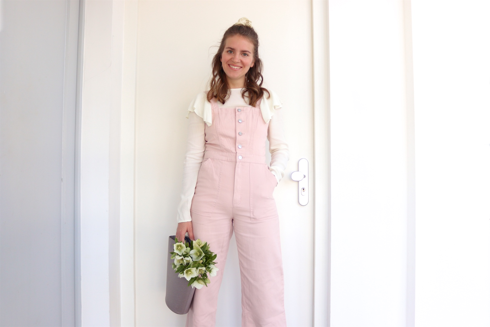 Pink Jumpsuit. Fashion Blogger Girl by Style Blog Heartfelt Hunt. Girl with blond half-up half-down loose waves and scrunchie wearing a pink jumpsuit, blouse with ruffles, Louis Vuitton bucket bag and lace-up heels.